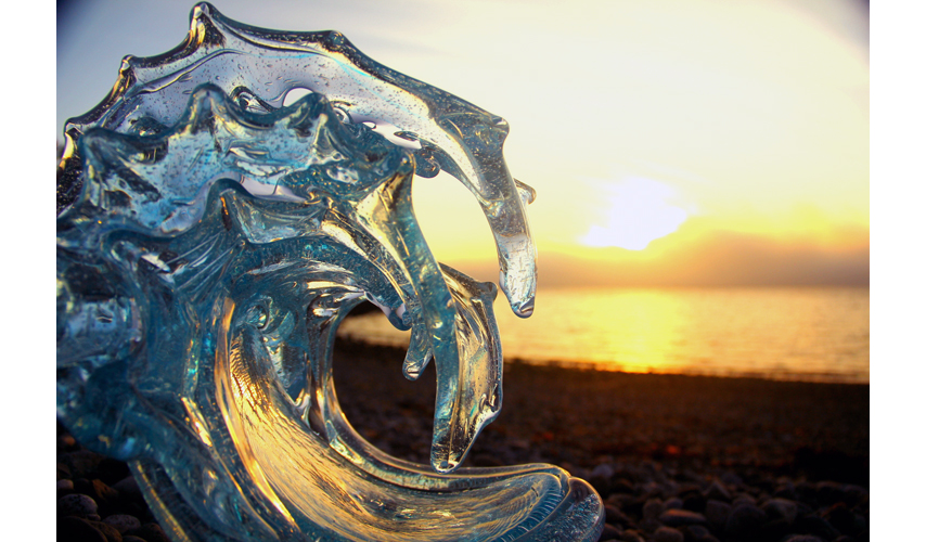 Double Champagne Glass Wave Sculpture on the Beach at sunset - David Wight Glass Art